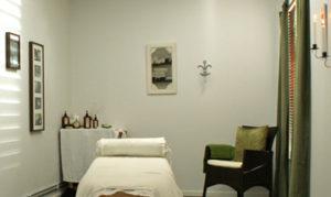 Ett dekorerat massagerum, med en massagebrits, stol, bord med oljor på, och tavlor hängandes på väggen. Rummet är enbart till för massage.