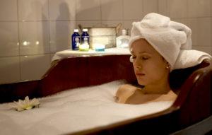 Kvinna som ligger i trädbadkar med produkter i bakgrunden. Bad hos Milstenen spa.