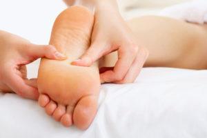 Fotbehandlingar som utförs på ett spa. Fotmassage utförs på en massagebrits